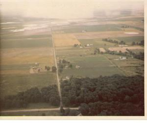 My house from the air, July 1970: My house is just to the right of the road in the center of the picture, surrounded by the little ring of trees. Note that our pond wasn't dug yet, and the farm across the road was still standing. (Don't die of nostalgia, anyone!)